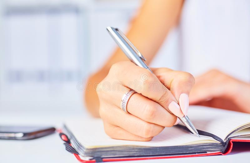 Giovane donna che lavora al suo scrittorio che prende il primo piano delle note Fuoco a disposizione che scrive su un blocco note fotografie stock