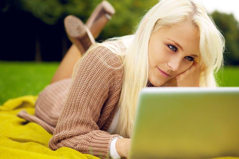 Giovane donna che lavora al suo taccuino in sosta immagine stock