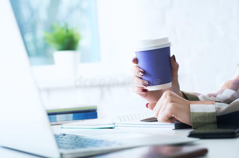 Giovane donna che lavora allo scrittorio con il computer portatile che tiene tazza di carta blu con caff? o il T Consegna appena  fotografia stock libera da diritti