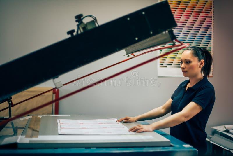 Giovane donna che lavora nella fabbrica di stampa immagine stock