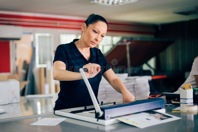 Giovane donna che lavora nella fabbrica di stampa immagine stock libera da diritti