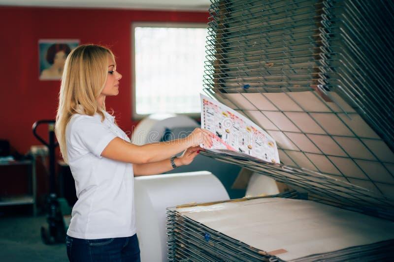 Giovane donna che lavora nella fabbrica di stampa fotografia stock