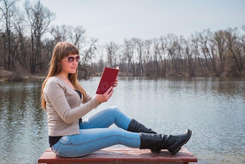 Giovane donna che legge il libro all'aperto in occhiali da sole, stile di vita quotidiano, fiume sui precedenti, molla, giorno so fotografie stock