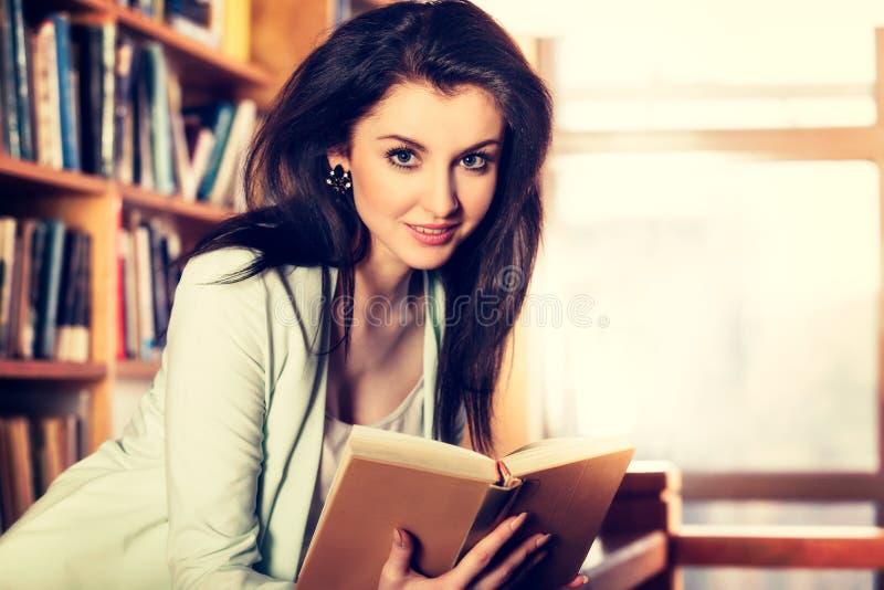 Giovane donna che legge un libro davanti agli scaffali per libri fotografia stock