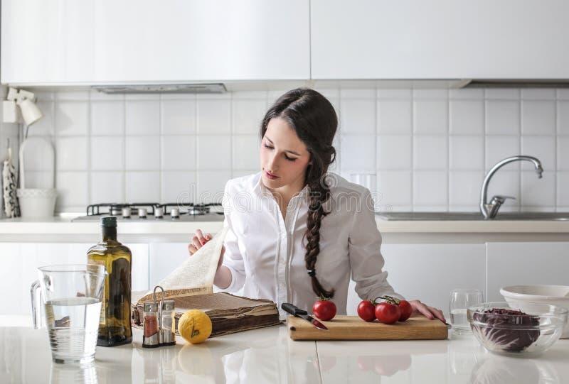 Giovane donna che legge un libro del cuoco immagini stock