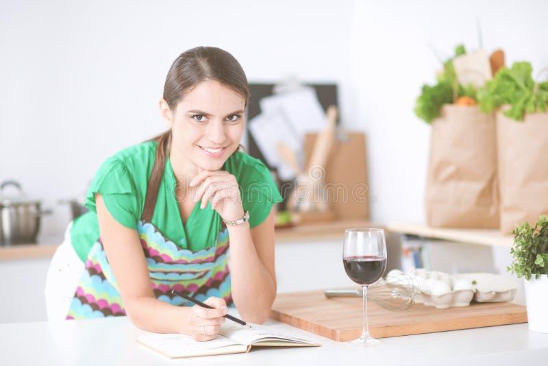 Giovane donna che legge un libro di ricetta nella cucina immagini stock libere da diritti