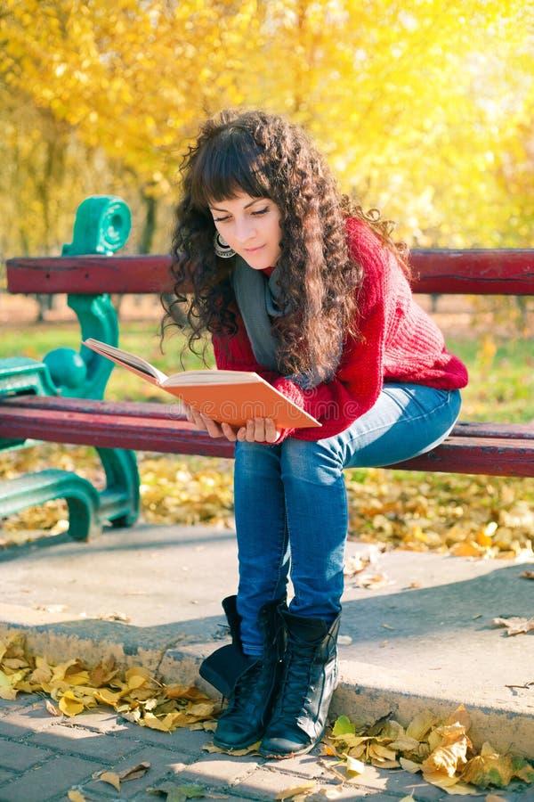 Giovane donna che legge un libro nel parco di autunno fotografia stock libera da diritti