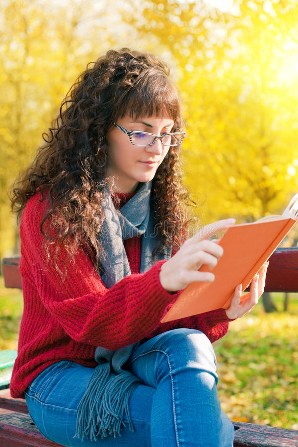 Giovane donna che legge un libro nel parco di autunno immagine stock libera da diritti