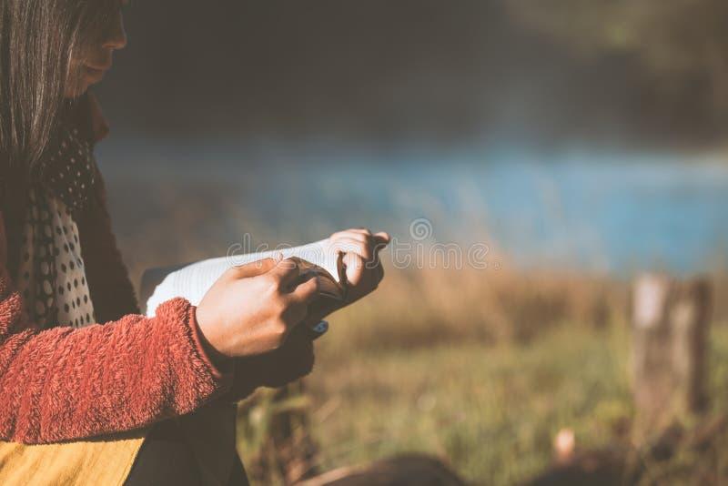 Giovane donna che legge un libro nel parco naturale con freschezza fotografia stock libera da diritti