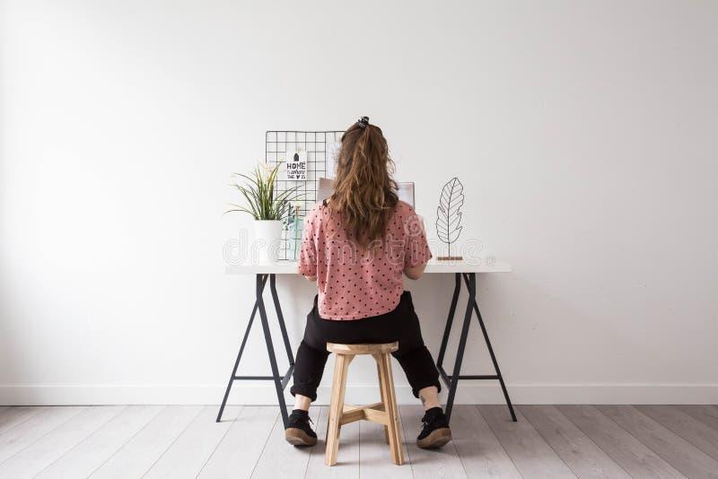 Giovane donna che legge una rivista in una stanza bianca moderna fotografia stock libera da diritti