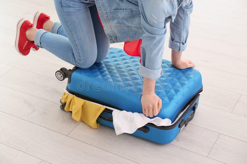 Giovane donna che lotta per chiudere valigia immagini stock