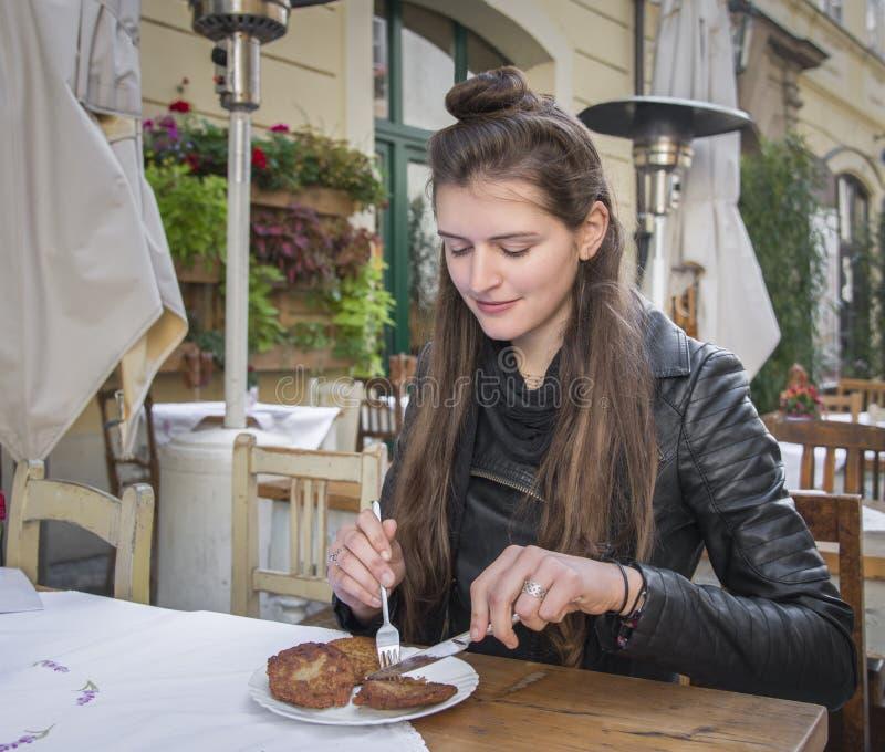 Giovane donna che mangia al ristorante all'aperto fotografia stock