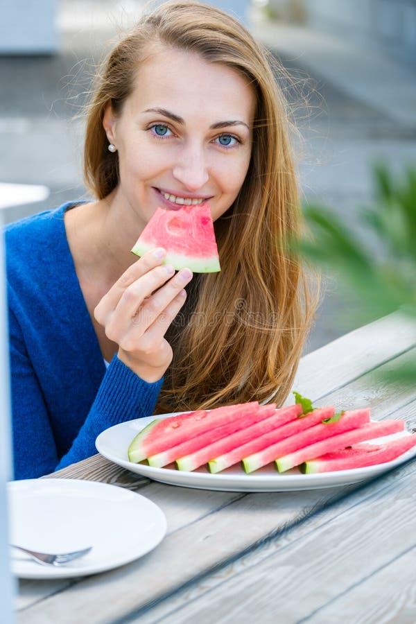 Giovane donna che mangia anguria fotografia stock
