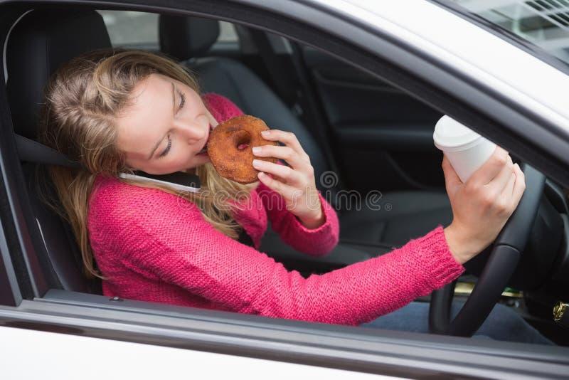 Giovane donna che mangia caffè e ciambella immagini stock libere da diritti