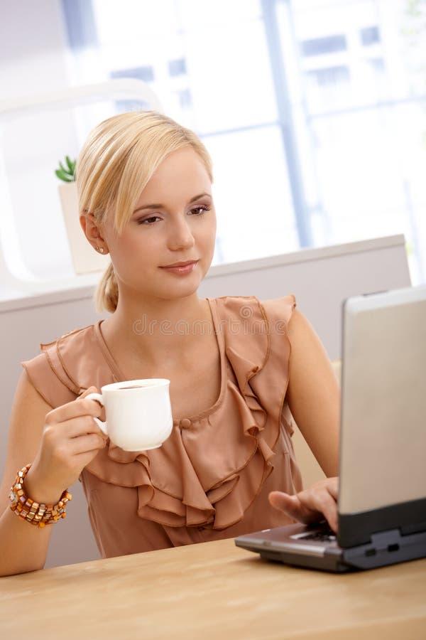 Giovane donna che mangia caffè per mezzo del computer portatile immagini stock libere da diritti