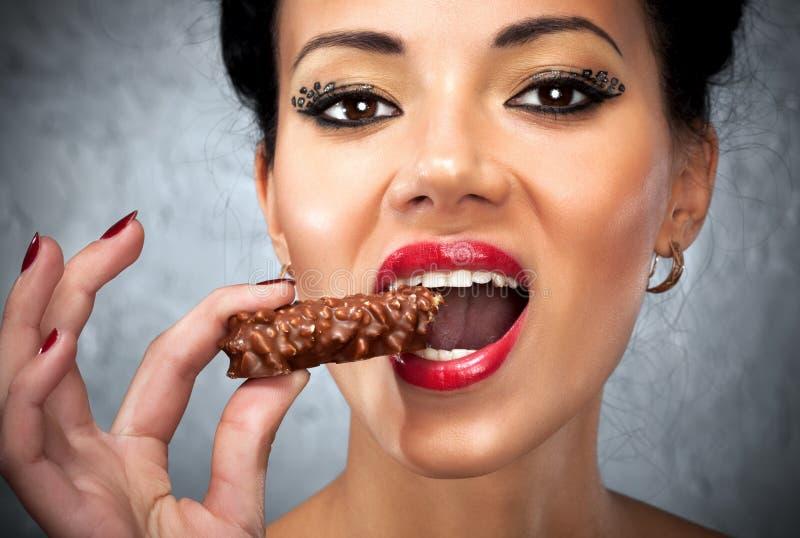 Giovane donna che mangia dolce fotografia stock libera da diritti