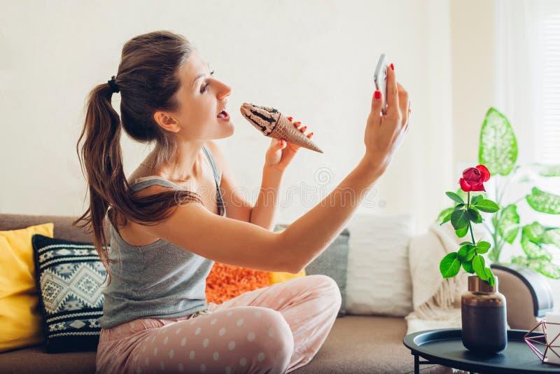 Giovane donna che mangia gelato al cioccolato in cono che si siede sullo strato a casa e che prende selfie facendo uso dello smar fotografie stock