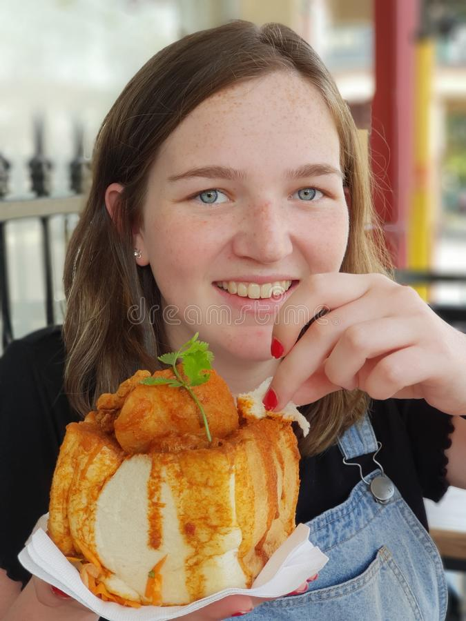 Giovane donna che mangia gli alimenti a rapida preparazione del cibo del coniglietto fotografia stock