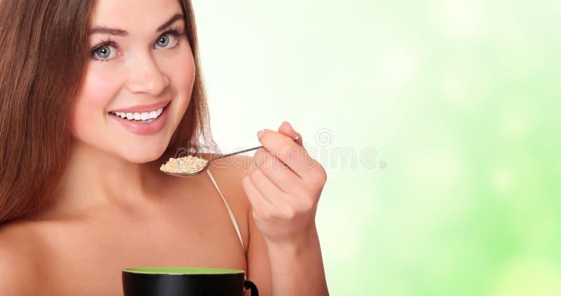 Giovane donna che mangia i fiocchi di avena fotografia stock