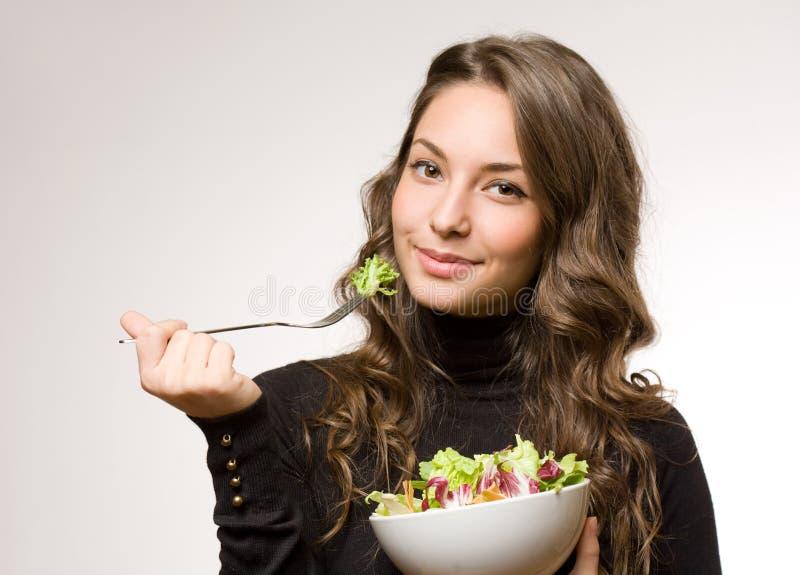 Giovane donna che mangia insalata. fotografie stock libere da diritti