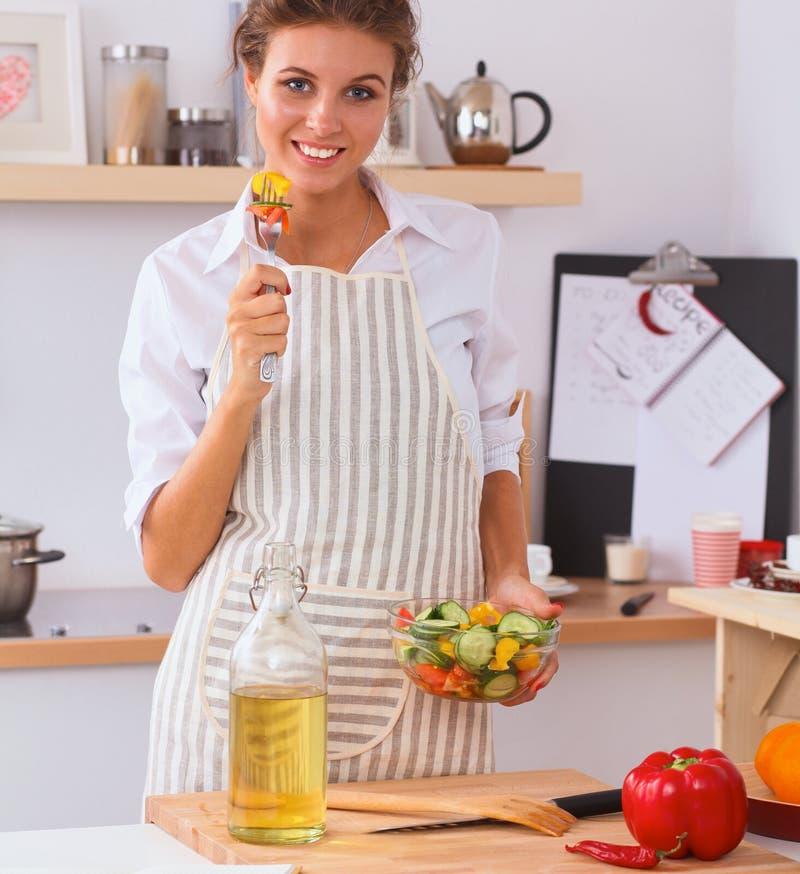Giovane donna che mangia insalata fresca in cucina moderna immagine stock libera da diritti