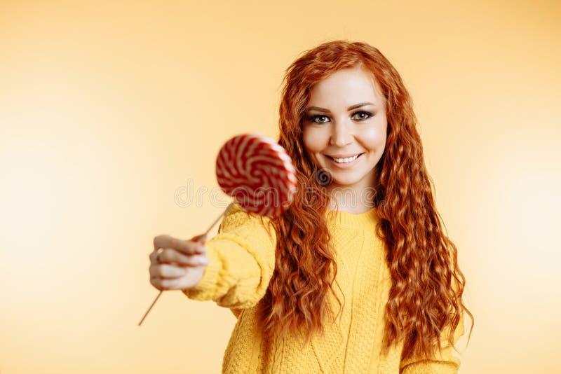 Giovane donna che mangia la lecca-lecca della caramella fotografia stock