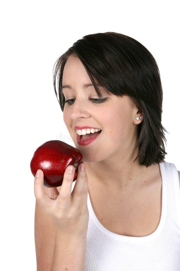 Giovane donna che mangia mela rossa fotografia stock libera da diritti