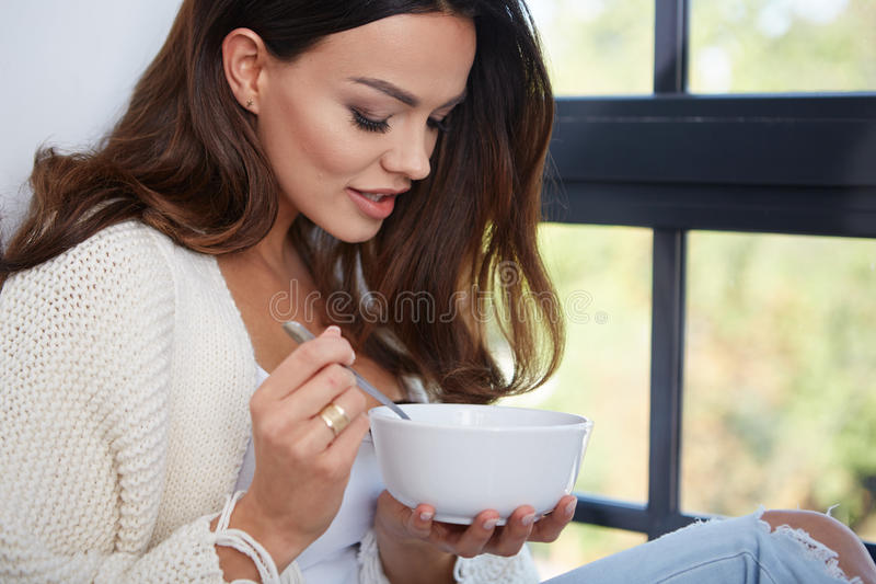 Giovane donna che mangia minestra fotografia stock