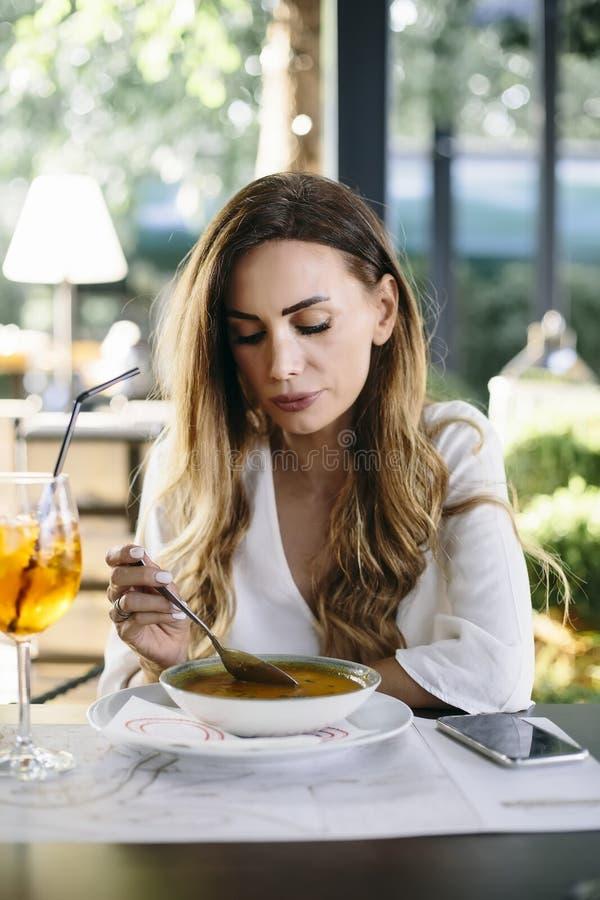 Giovane donna che mangia minestra in ristorante immagine stock libera da diritti