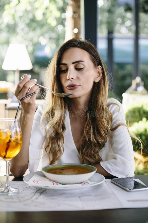 Giovane donna che mangia minestra in ristorante fotografie stock