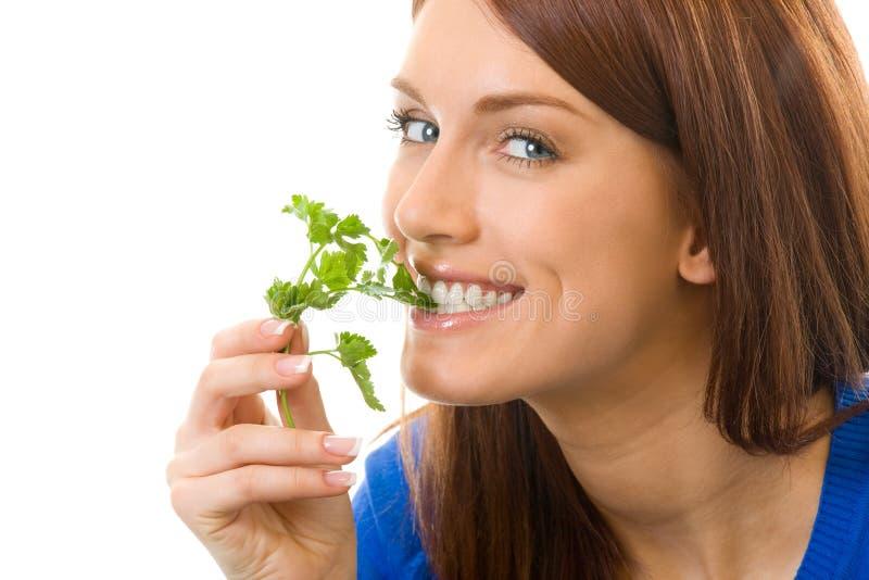 Giovane donna che mangia prezzemolo fotografia stock