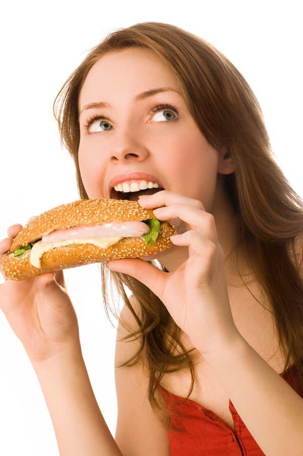 Giovane donna che mangia un hot dog fotografia stock libera da diritti