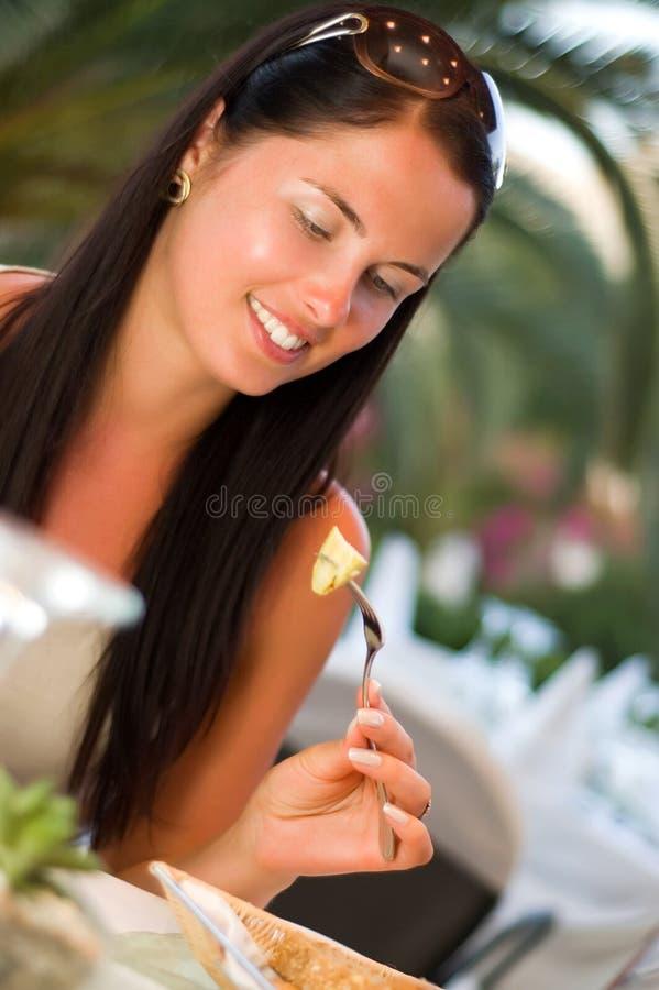 Giovane donna che mangia un'insalata al ristorante fotografie stock libere da diritti