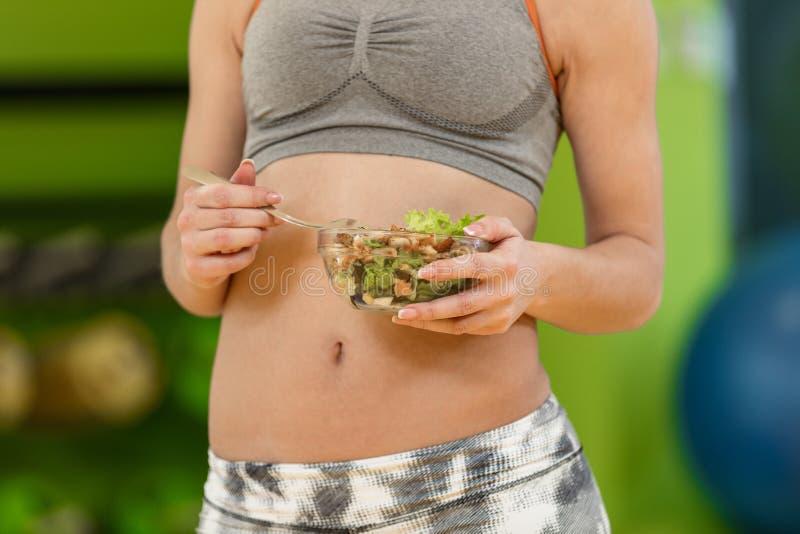 Giovane donna che mangia un'insalata sana delle verdure dopo l'allenamento Forma fisica e concetto sano di stile di vita immagini stock