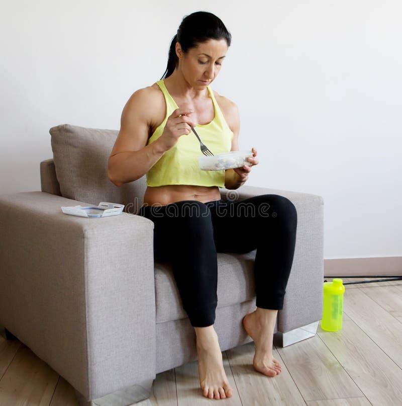 Giovane donna che mangia una macedonia sana dopo l'allenamento fotografia stock libera da diritti