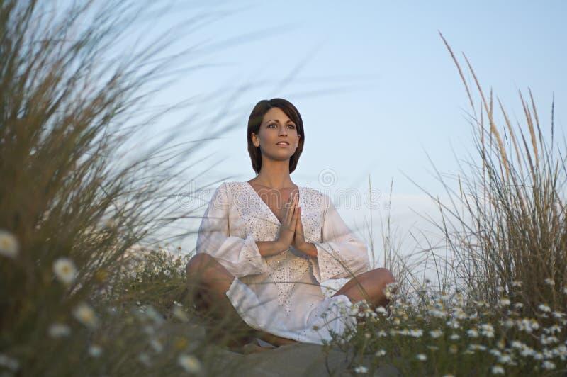 Giovane donna che medita su spiaggia fotografia stock