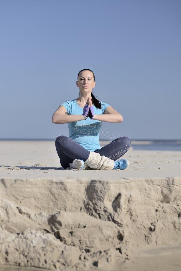 Giovane donna che medita su spiaggia fotografie stock libere da diritti