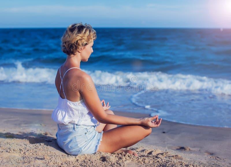 Giovane donna che medita su spiaggia, pilastro nella posizione di loto al sunri immagine stock libera da diritti
