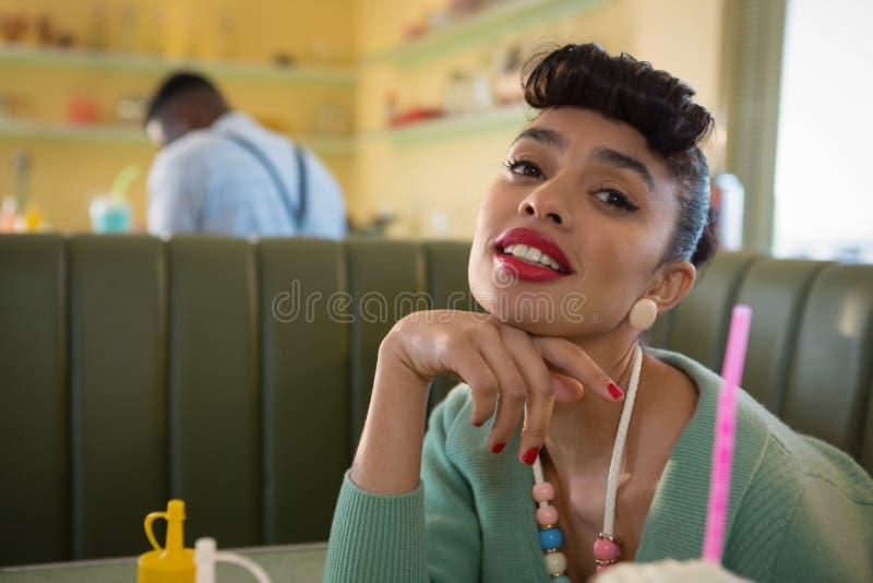 Giovane donna che mette il suo mento sul pugno che esamina macchina fotografica al ristorante fotografia stock