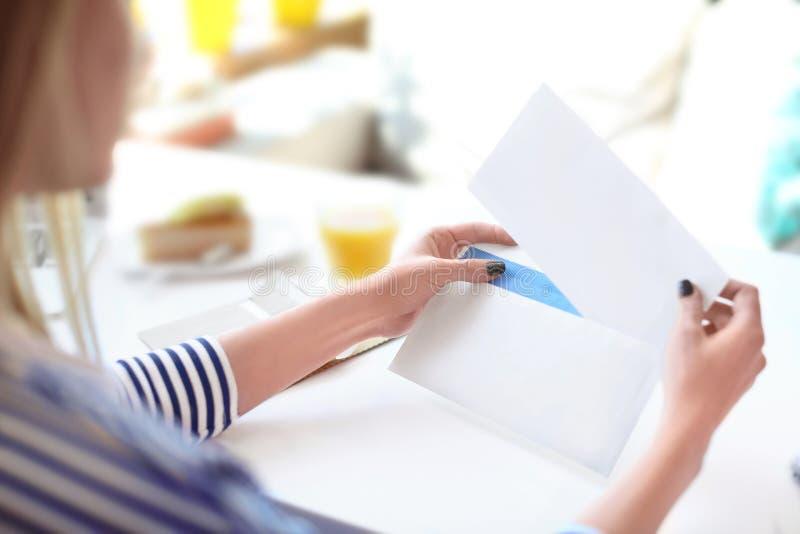Giovane donna che mette lettera nella busta alla tavola in caffè consegna di posta immagine stock libera da diritti