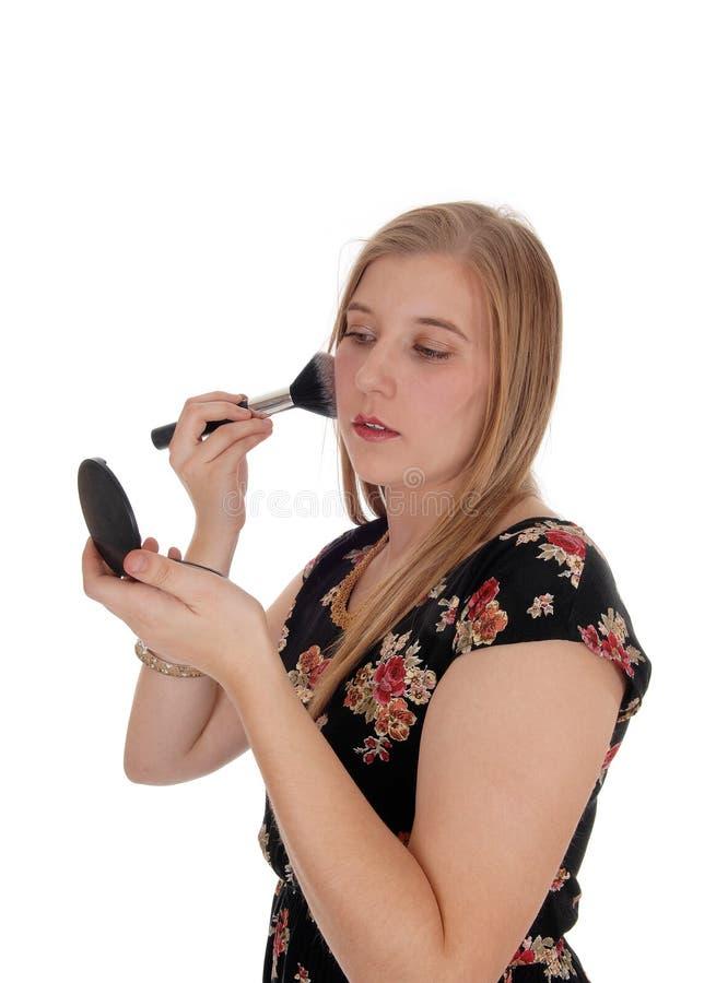 Giovane donna che mette trucco sul suo fronte fotografie stock libere da diritti