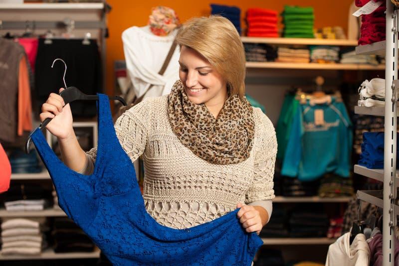 Giovane donna che misura un vestito che si guarda dentro di mattina fotografia stock