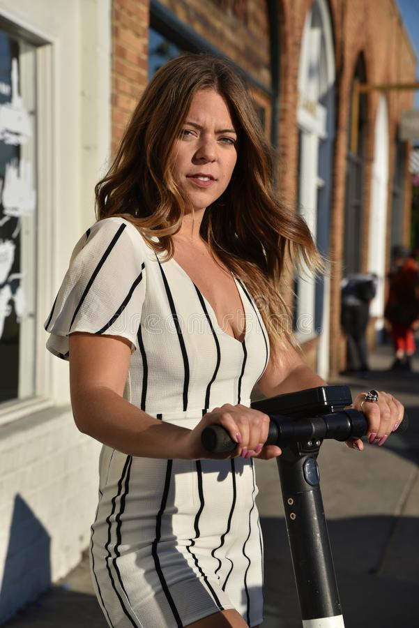 Giovane donna che monta un motorino elettrico immagine stock libera da diritti