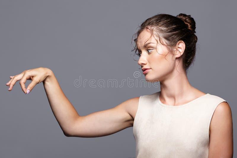 Giovane donna che mostra e che presenta lo spazio della copia dalle dita fotografie stock libere da diritti