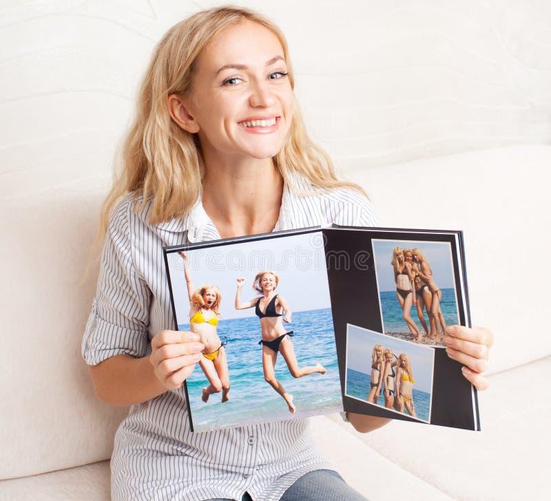Giovane donna che mostra il libro della foto fotografie stock