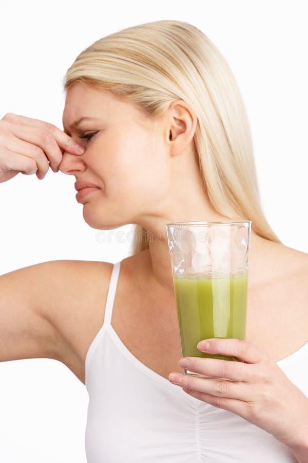 Giovane donna che non gode della bevanda sana in studio fotografia stock