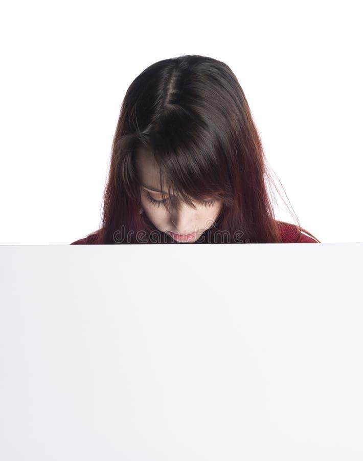 Giovane donna che osserva giù il bordo bianco in bianco fotografie stock