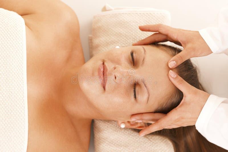Giovane donna che ottiene massaggio capo immagine stock libera da diritti