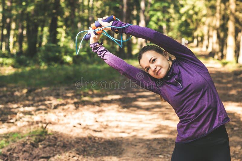 Giovane donna che pareggia e che fa gli esercizi nella foresta soleggiata fotografie stock libere da diritti
