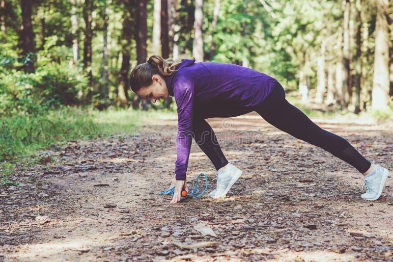 Giovane donna che pareggia e che fa gli esercizi nella foresta soleggiata immagini stock